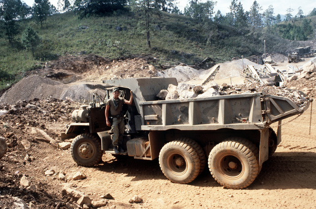 A West Virginia Army National Guard soldier poses on a dump truck being used for road construction during Task Force III, a civic action program in which the guard is also providing health and veterinary services for residents of the Puenta Grande area