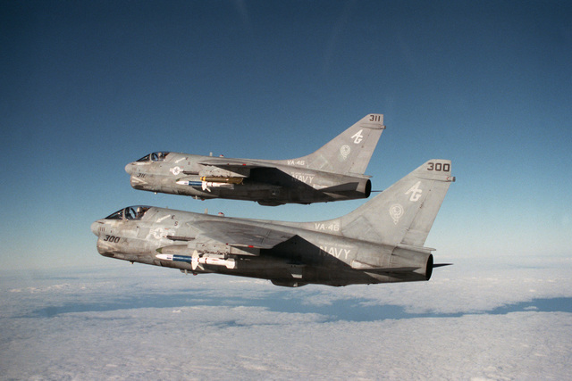 An air-to-air left side view of two Attack Squadron 46 (VA-46) A-7E Corsair II aircraft flying in formation.  The aircraft are armed with AGM-45 Shrike missiles
