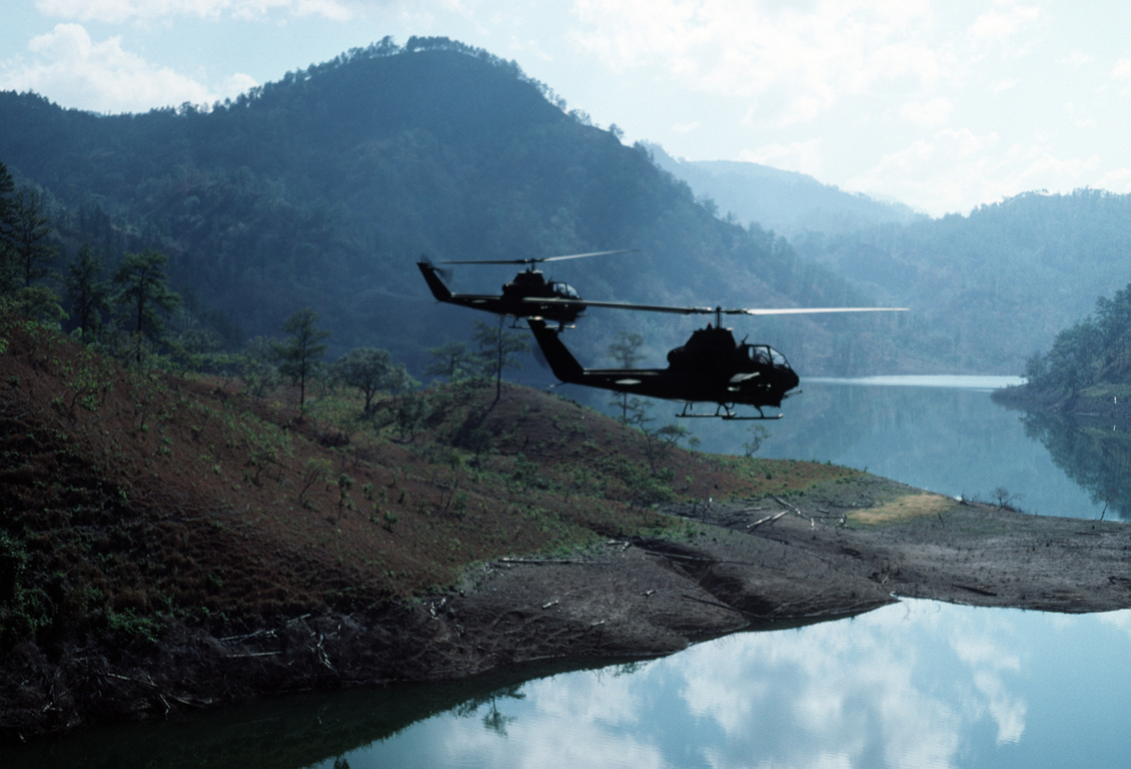 An air-to-air right side view of two AH-1 Cobra helicopters from the 17th Air Cavalry Brigade in flight for a combat run on the Camp Del Balomple Range.  President Ronald Reagan mobilized US Exercise Task Force DRAGON/GOLDEN PHEASANT, consisting of both the 82nd Airborne Division and the 7th Light Infantry Division, to help discourage Nicaraguan forces from entering Honduras