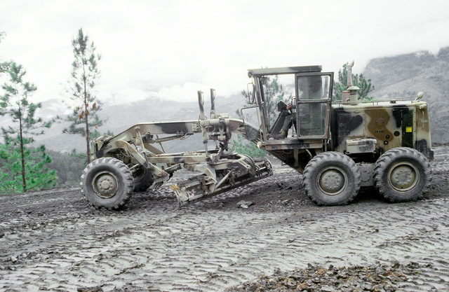An earthmoving scraper operated by a member of the West Virginia National Guard is used for road construction during Task Force III, a civic action program in which the guard is also providing health and veterinary services for residents of the Puenta Grande area