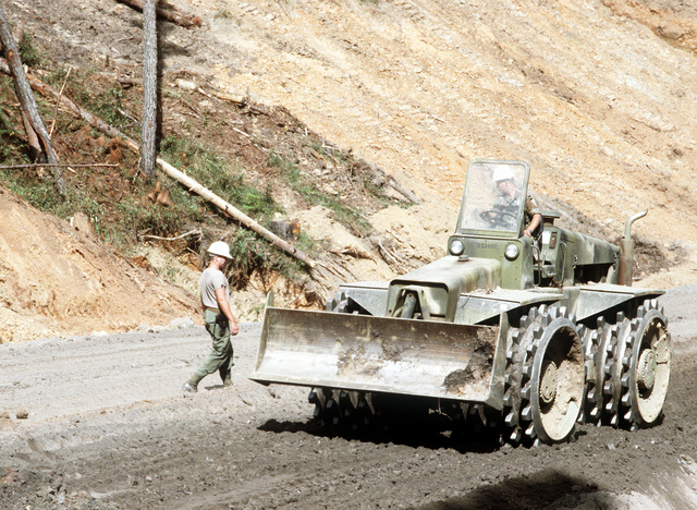 An embankment compacter tamps a roadbed for one of a network of roads being built by the West Virginia Army National Guard during Task Force III, a civic action program in which the guard is also providing health and veterinary services for residents of the Puenta Grande area