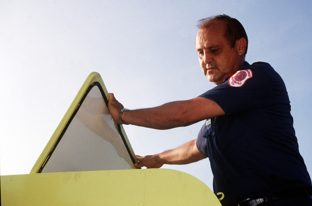 Cecil Lockhardt inspects a compartment atop one of the air station fire department's vehicles