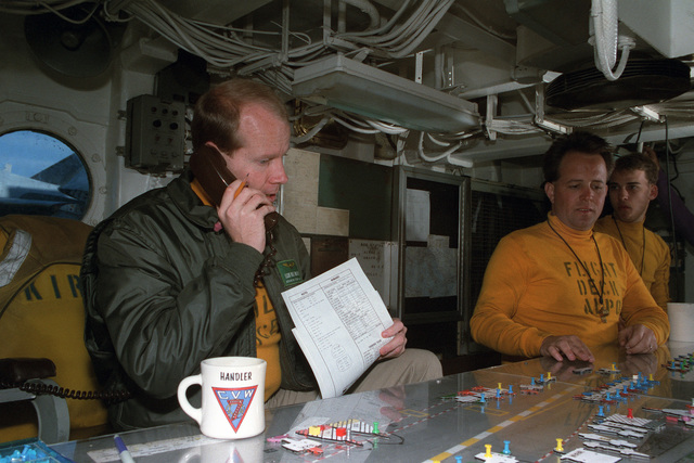 Lieutenant Commander (LCDR) W.J. McKeever, left, takes a call in flight deck control on board the US Navy (USN) Nuclear-powered Aircraft Carrier USS DWIGHT D. EISENHOWER (CVN 69).  McKeever and his assistants use the board in front of them to track the placement of aircraft on the flight deck
