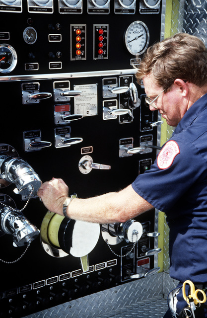 LT Rosbottom closes a discharge valve on the side of one of the air station fire department's firefighting vehicles