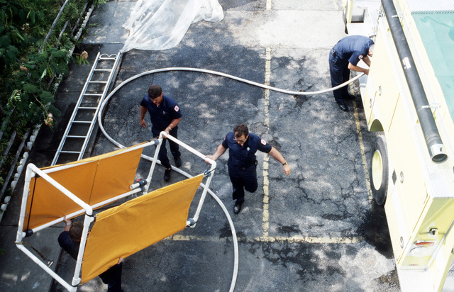 Member's of the air station fire department dismantle a portable decontamination shower after a hazardous materials incident response drill