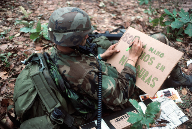 """Private First Class (PFC) Grimaldi from the 1ST Battalion, the 504th Parachute Infantry Regiment, 82nd Airborne Division, makes a sign in Spanish that says,""""82nd Airborne, the hand of God in Honduras,""""for his base camp.  President Ronald Reagan mobilized US Exercise Task Force DRAGON/GOLDEN PHEASANT, consisting of both the 82nd Airborne Division and the 7th Light Infantry Division, to help discourage Nicaraguan forces from entering Honduras"""