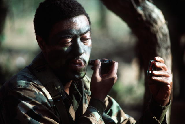 STAFF Sergeant (SSG) Glen White from the 1ST Battalion, the 504th Parachute Infantry Regiment, 82nd Airborne Division, applies camouflage paint to his face during a field deployment.  President Ronald Reagan mobilized US Exercise Task Force DRAGON/GOLDEN PHEASANT, consisting of both the 82nd Airborne Division and the 7th Light Infantry Division, to help discourage Nicaraguan forces from entering Honduras