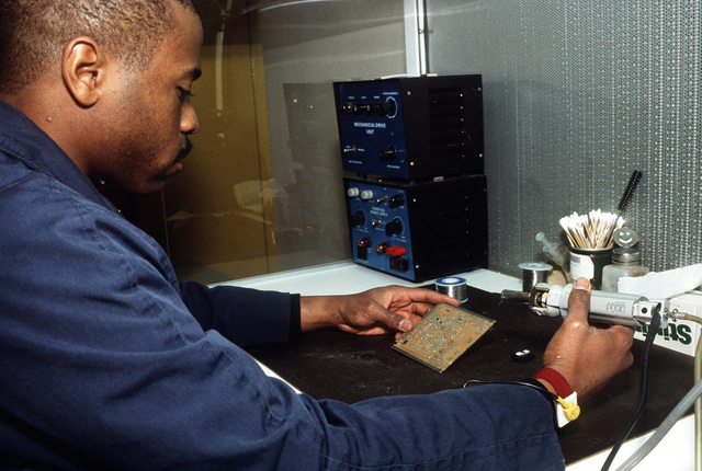 Aviation Electrician's Mate 2nd Class (AE2) Anthony J. Winters repairs a printed circuit board in an Aircraft Intermediate Maintenance Department repair shop