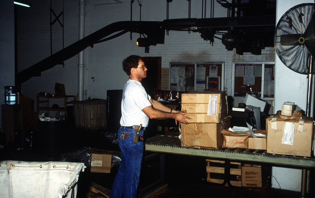 A civilian worker unpacks boxes in a Naval Supply Center warehouse
