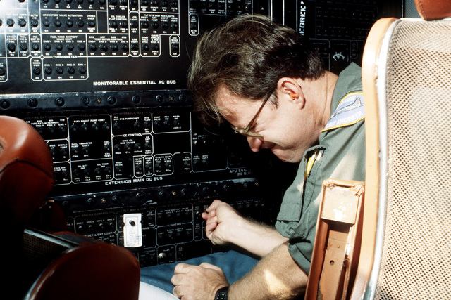Aviation Structual Mechanic 1ST Class (Flight Engineer) Downs checks fuses in a P-3C Orion aircraft cockpit