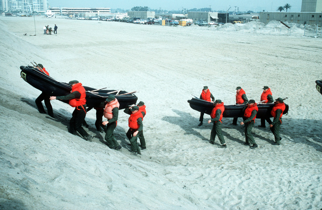 Trainees carry inflatable boats across the beach as they participate in a Basic Underwater Demolition/SEAL (BUD/S) exercise at Coronado Beach