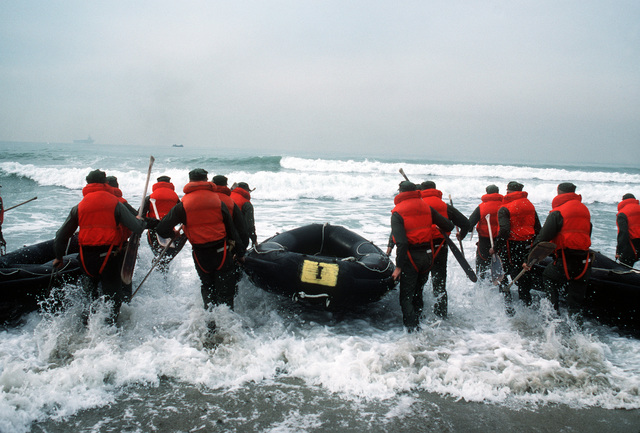 Trainees carry inflatable boats out to sea as they participate in a Basic Underwater Demolition/SEAL (BUD/S) exercise at Coronado Beach