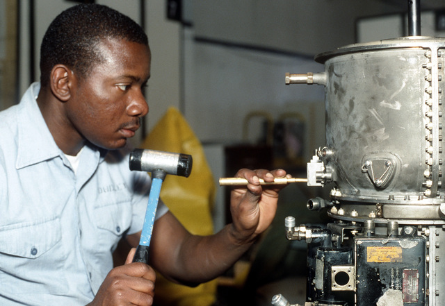 Aviation Machinist's Mate AIRMAN Lindsay D. Dudley D. taps a gasket into place on a T-58 turboshaft helicopter engine. Dudley works for the air station's Aircraft Intermediate Maintenance Department