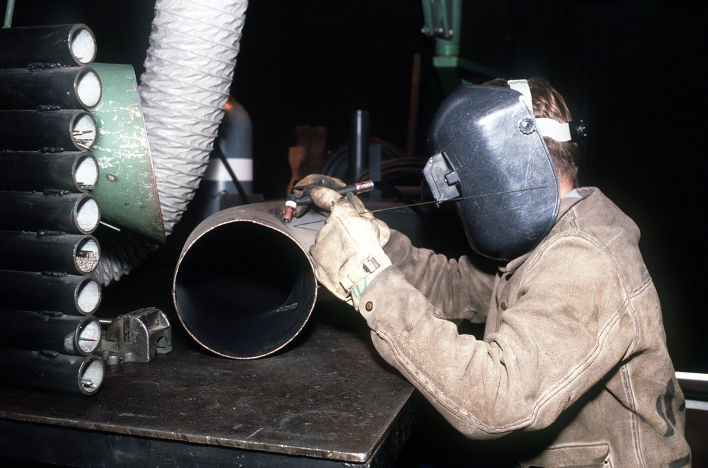 Aviation Structural Mechanic 2nd Class Tye A. boyd gets ready to weld an exhaust stack in an Aircraft Intermediate Maintenance Department shop