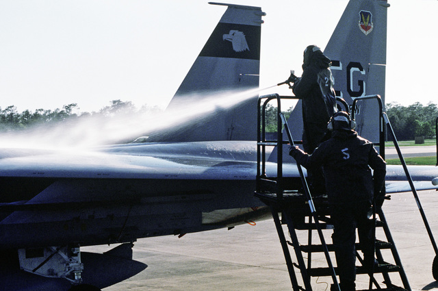 Aircraft support personnel of the 33rd Tactical Fighter Wing use neutralizing chemicals to hose down an F-15 Eagle aircraft during a decontamination exercise, part of the chemical warfare Exercise NOMAD THRUST 88.  The men are wearing nuclear-biological-c