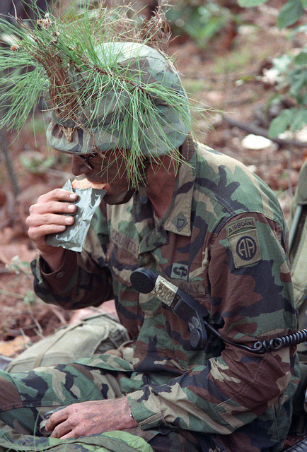 A radio operator from the 82nd Airborne Division, his handset hooked to a pocket, eats a Meal, Ready-to-Eat (MRE) during Operation Golden Pheasant