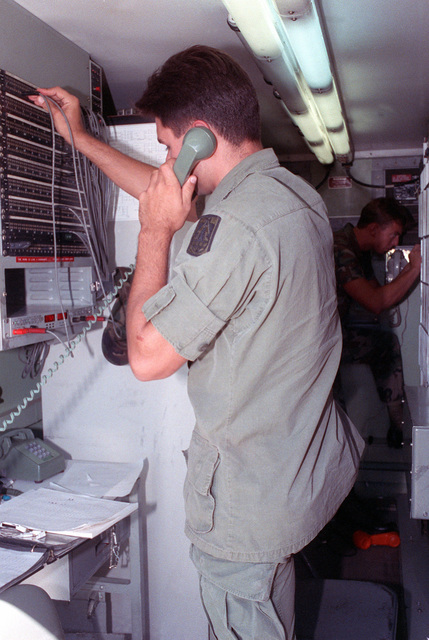 A soldier checks a telephone connection in a telephone operations center inside a transportable shelter during Operation Golden Pheasant