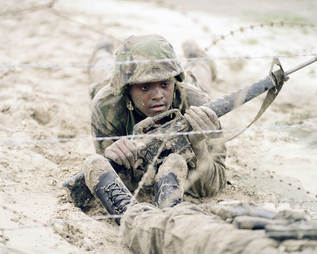 A woman Marine armed with an M16A1 rifle encounters the barbed-wire obstacle on the infiltration course during a field training exercise