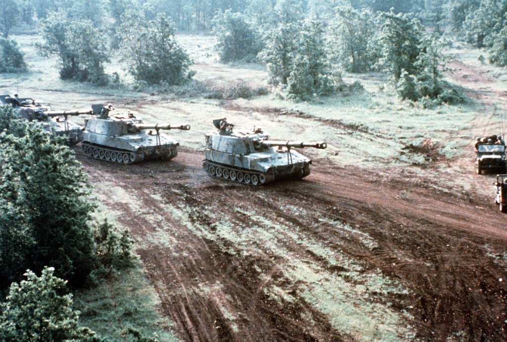 A line of M-109 self-propelled 155mm howitzers roll down a dirt road during maneuvers