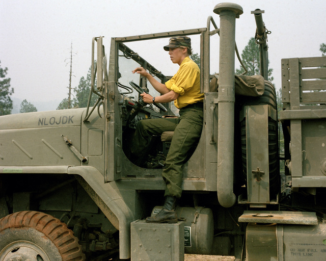 First Lieutenant (1LT) Michelle Biddle, Company D, 7th Supply and Transport Battalion, steps out of the driver's door of a 2 1/2-ton truck at camp headquarters during the deployment of the 7th Infantry Division (Light), to fight a fire near Cave Junction.  Biddle's company provides logistical support, transportation, fuel, water, forklift, maintenance and laundry services for the firefighters