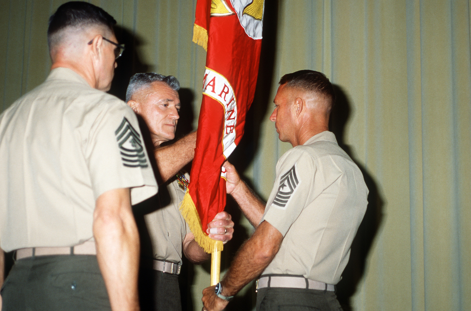 Sergeant Major (SGM) David W. Sommers, incoming sergeant major of the Command and STAFF College, receives the command flag from Colonel (COL) Wesley Fox while an unidentified sergeant major looks on during the change of command ceremony