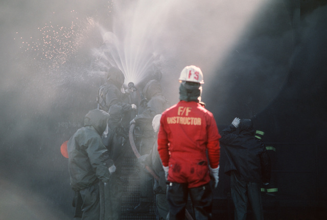 An instructor observes as students fight a fire during a firefighting drill at the Fleet Mine Warfare Training Center (FMWTC).  The center, the only one of its kind in the Navy, trains new recruits as well as experienced Sailors in areas such as mine assembly, fire fighting, damage control, minehunter operations, computer board repair and leadership/management programs