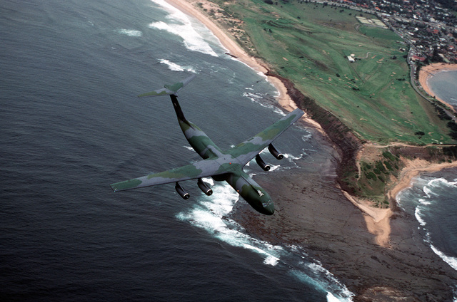 A C-141B Starlifter aircraft in flight over the coastline