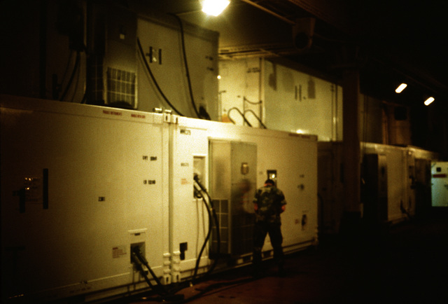A Marine checks an outlet on a shelter in the cargo hold of a Waterman class maritime pre-positioning ship during exercise Ocean Venture '88