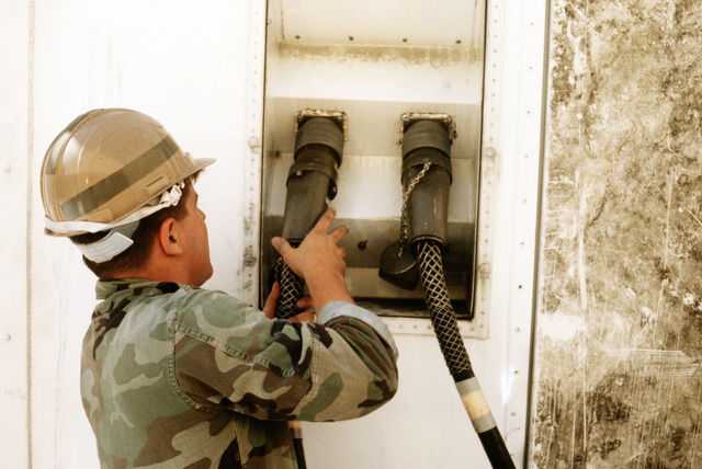 A Marine connects power cables to a shelter aboard the aviation logistic ship USNS WRIGHT (T-AVB 3) during exercise OCEAN VENTURE '88