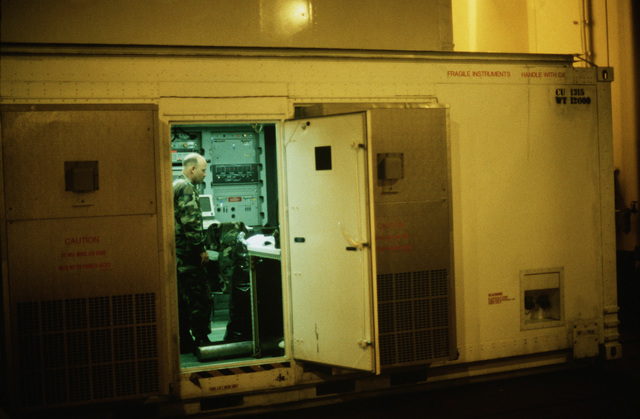 A Marine monitors instrument panels inside a shelter in the cargo hold of the maritime pre-positioning ship PFC EUGENE A. OBREGON (T-AK-3005) during exercise Ocean Venture '88