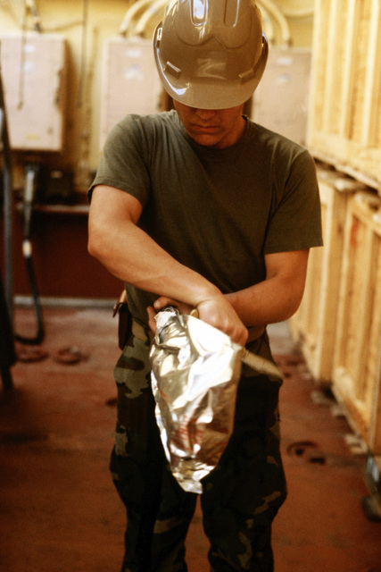 A Marine unwraps a protective foil covering from equipment aboard the aviation logistic ship USNS WRIGHT (T-AVB 3) during exercise OCEAN VENTURE '88