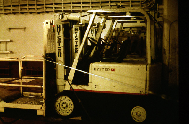 Forklifts are parked in the cargo hold of the maritime pre-positioning ship PFC EUGENE A. OBREGON (T-AK-3005) during exercise Ocean Venture '88