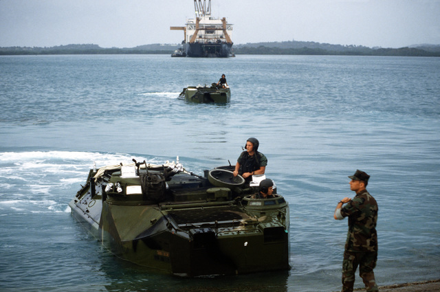 Marines come shore in AAVP-7A1 assault amphibian vehicles as a harbor tug maneuvers a maritime pre-positioning ship during exercise Ocean Venture '88