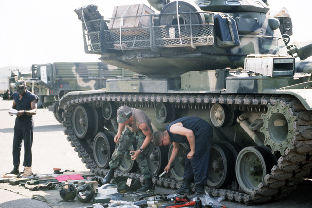 Marines conduct an inventory to ensure that the gear needed to operate and maintain an M-60 tank is stored with the vehicle. Vehicles, weapons and equipment were brought ashore from maritime pre-positioning ships as part of exercise Ocean Venture '88