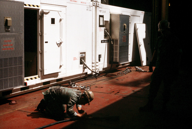 Marines inspect power cables prior to connecting them to shelters aboard the aviation logistic ship USNS WRIGHT (T-AVB 3) during exercise OCEAN VENTURE '88