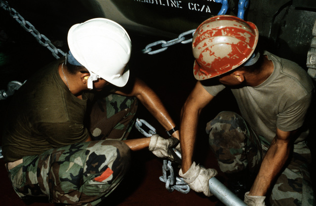 Marines use chains to secure equipment in the cargo hold of the maritime pre-positioning ship PFC EUGENE A. OBREGON (T-AK-3005) during exercise Ocean Venture '88