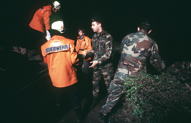 Members of the 435th Security Police Squadron, Rhein-Main Air Base, and German Fire Department personnel shore up a weakened dam complex with sandbags at the ESWE Waterworks plant along the swollen Rhine River. The river, which reached its highest level i