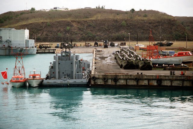 Two rows AAVP-7A1 amphibious assault vehicles are staged on a pier prior to being placed back aboard a maritime pre-positioning ship during exercise Ocean Venture '88