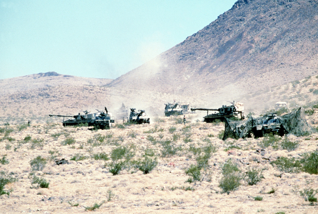 A battery of M-109 155mm self-propelled howitzers take up positions in the desert during a training exercise at the National Training Center