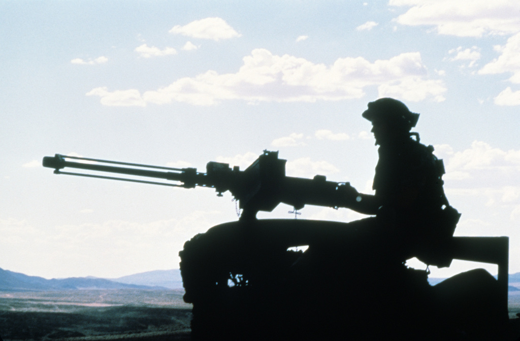 A gunner mans an M2 .50-caliber machine gun mounted on a turret of an armored vehicle at the National Training Center.  The gun is fitted with a device for firing blanks