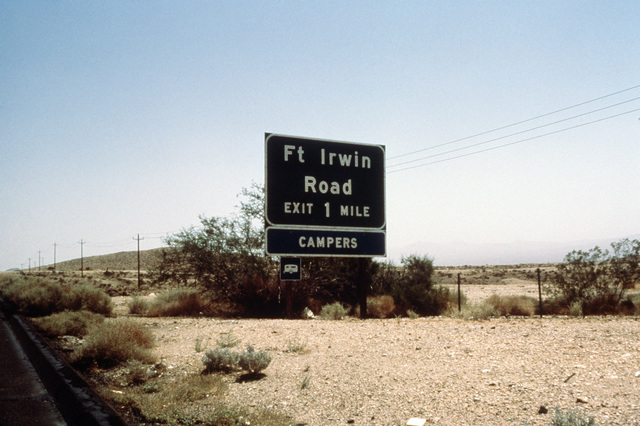 A road sign directing motorists to Fort Irwin Road and a campsite