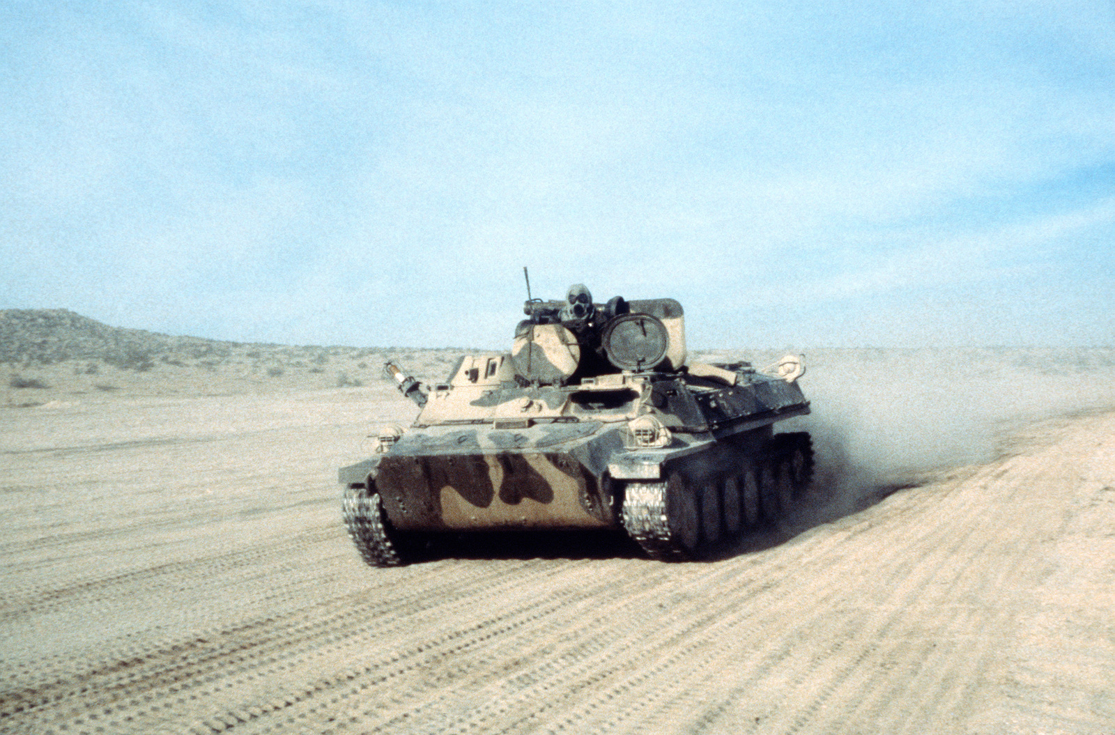 A Soviet MT-LB multipurpose tracked vehicle moves along a dirt road during an exercise at the National Training Center.  The vehicle is used by the 177th Armored Brigade in their role as an opposing force