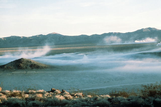 An elevated view of the desert floor shrouded in early morning mist at the National Training Center