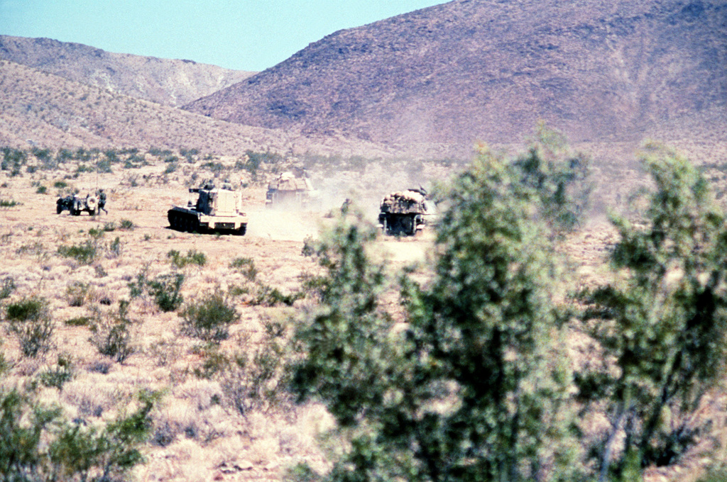 An M-109 155mm self-propelled howitzer and an M-578 light armored recovery vehicles roll through the desert during a training exercise at the National Training Center