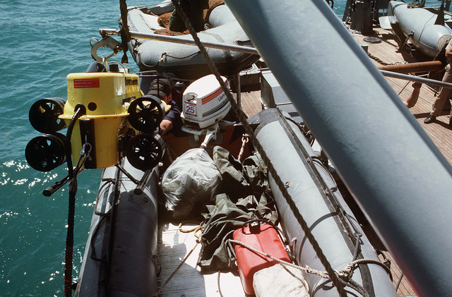 Crew members haul a minesweeping device aboard the ocean minesweeper USS ILLUSIVE (MSO 448)