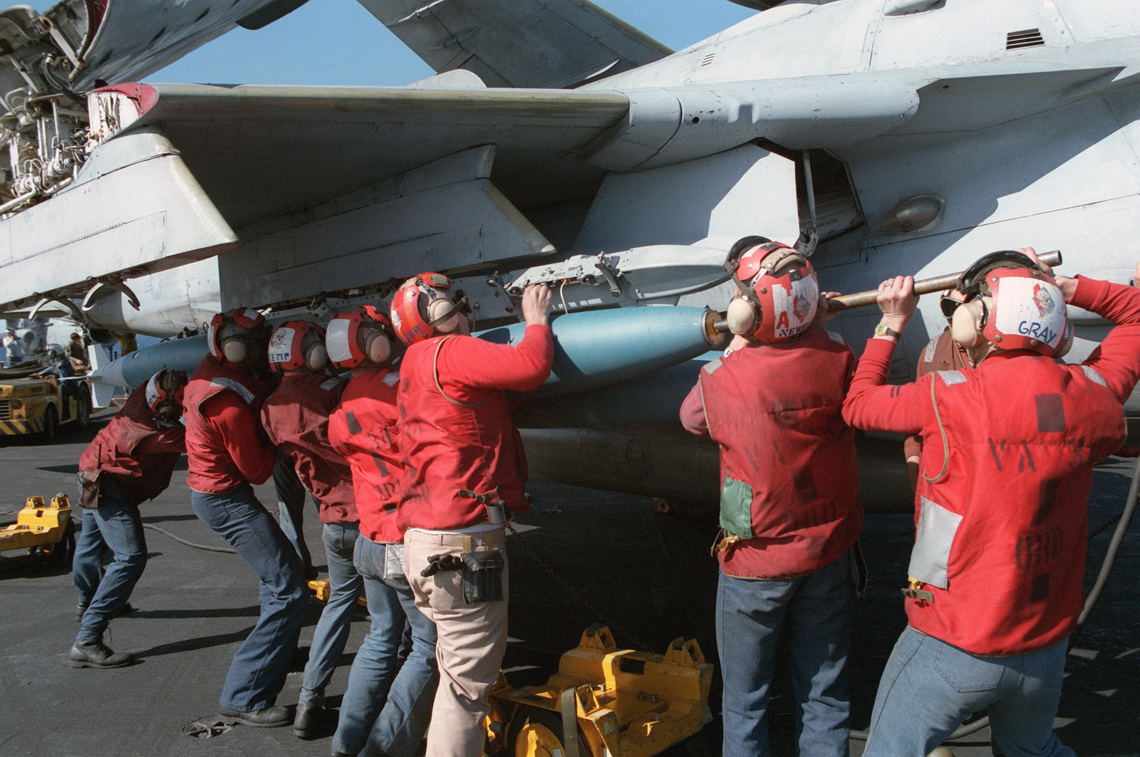 Ordnancemen from Attack Squadron 34 (VA-34) load a Mark 80-series bomb onto an inboard wing pylon of an A-6E Intruder aircraft on board the US Navy (USN) Nuclear-powered Aircraft Carrier USS DWIGHT D. EISENHOWER (CVN 69)