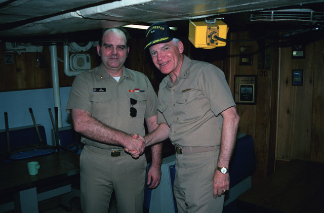 Rear Admiral (RADM) (upper half) Francis N. Smith, commander, Naval Reserve Force, shakes hands with CHIEF PETTY Officer (CPO) Ron Duncan onboard the ocean minesweeper USS ESTEEM (MSO 438) during his tour of the Persian Gulf