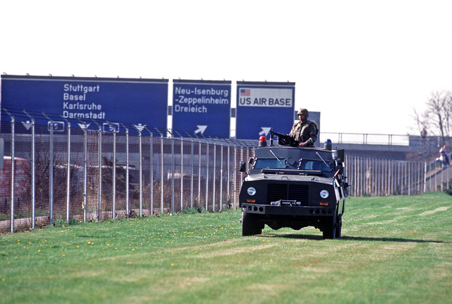 AIRMAN First Class (A1C) Lester Brown of the 435th Security Police Squadron stands behind the M60 machine gun turret of a Peacekeeper armored personnel carrier, inside the perimeter fence.  His patrol is part of tightened base security in the wake of terr