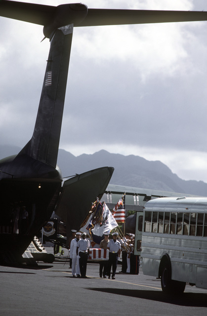 The remains of 27 service members missing in action are carried from a C-141B Starlifter aircraft to a bus as an all service color guard displays the colors in the largest turnover of MIAs since meetings began with North Vietnam in 1981