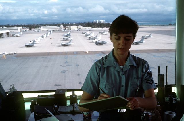 A female Navy air traffic controller makes a notation while on duty in control tower
